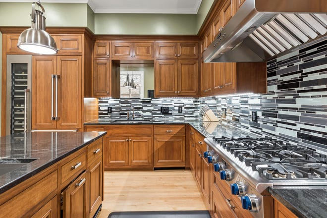 Different textures in the gourmet kitchen contrast beautifully. The wood cabinetry, dark granite counters, shining glass backsplash and stainless steel appliances combine in a great design.