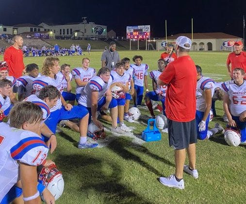 Heritage junior varsity football players meet on the field after Thursday's 13-6 victory at Decatur.