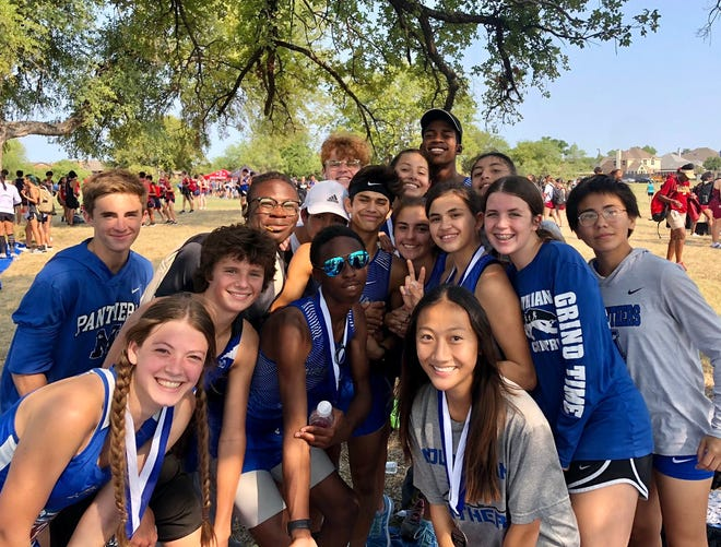 The Midlothian High School cross-country team shows off its hardware at the North Crowley Invitational on Friday in Fort Worth. Senior Avalon Mitchell (front, right) placed second in the varsity girls' race in a time of 20:52.14.