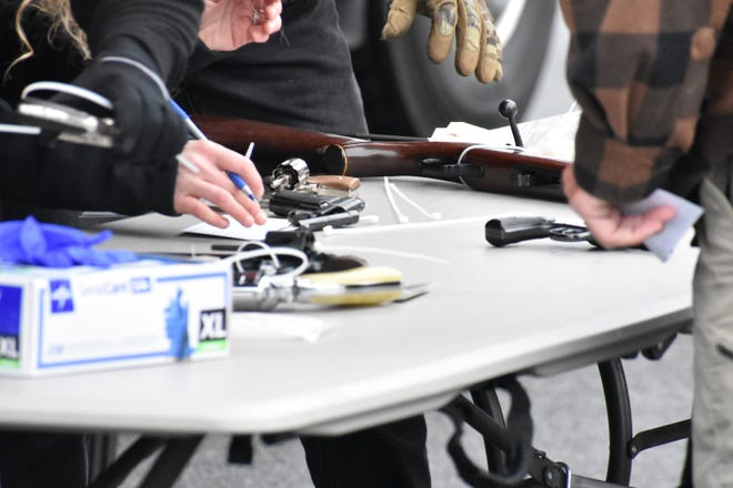Staff from the state Attorney General's Office catalogue and secure firearms Friday during a buyback event in Utica, Saturday, Oct. 19, 2019.