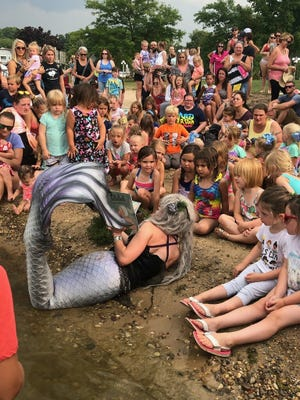 A mermaid visits preschoolers at a beach as part of a recent Story Hour program offered by the Boyne District Library.