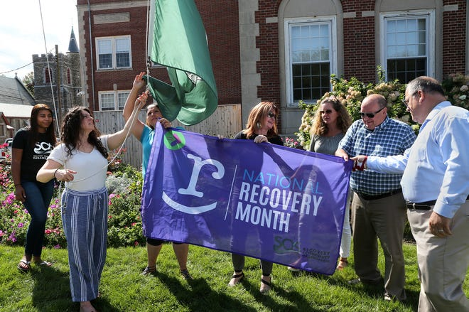 In recognition of Recovery Month, a flag was raised at Dover City Hall Tuesday afternoon Sept. 14, 2021. Mary Boisse of SOS Recovery and Goodwin Community Health, at left, gets ready to raise the flag.