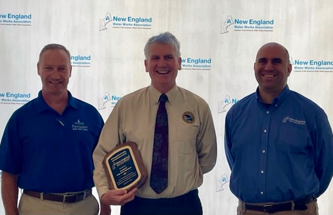 New England Water Works Vice President James DeCelles (left) and NEWWA Board member Thomas LeCourt (right) present the NEWWA award to Deputy Director Brian Goetz recognizing the City of Portsmouth.