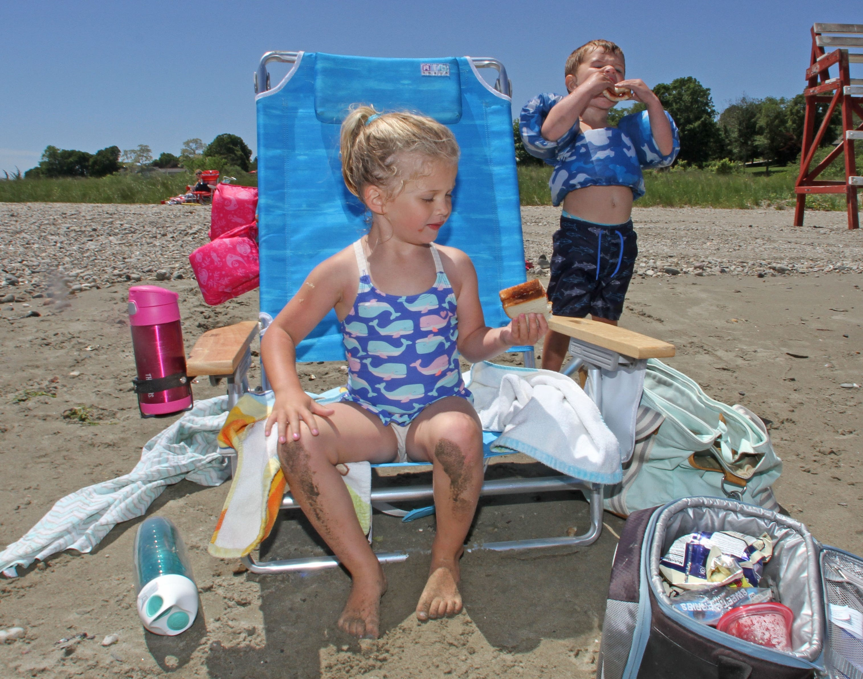 Ava, 4, and Trevor Siclari, 2, of East Providence, enjoy a peanut butter sandwich for lunch while at Sandy Point Beach, along the Sakonnet River, Portsmouth. Their mother Melissa Siclari likes the quiet beach.
