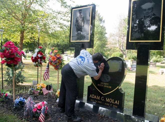 Fred Molai, of Munroe Falls, kisses his son's face etched on the headstone. He has fought for years to have an elaborate graveside display at his son's grave in Standing Rock Cemetery and recently received a jury decision in his favor. A