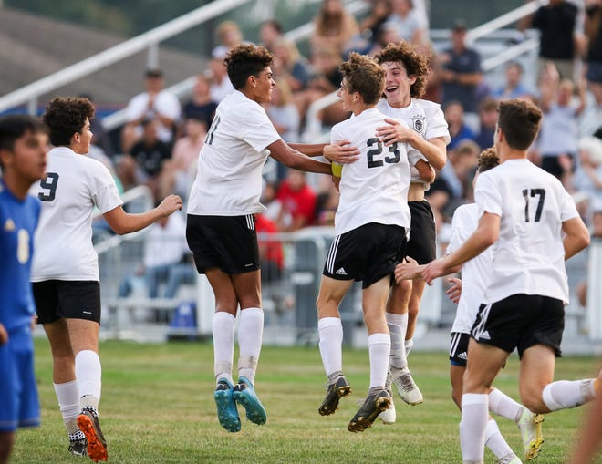 Penn teammates celebrate during a game against Elkhart last month. On Monday Penn defeated host Northridge, 3-1, in the boys 3A soccer sectional in Middlebury.
