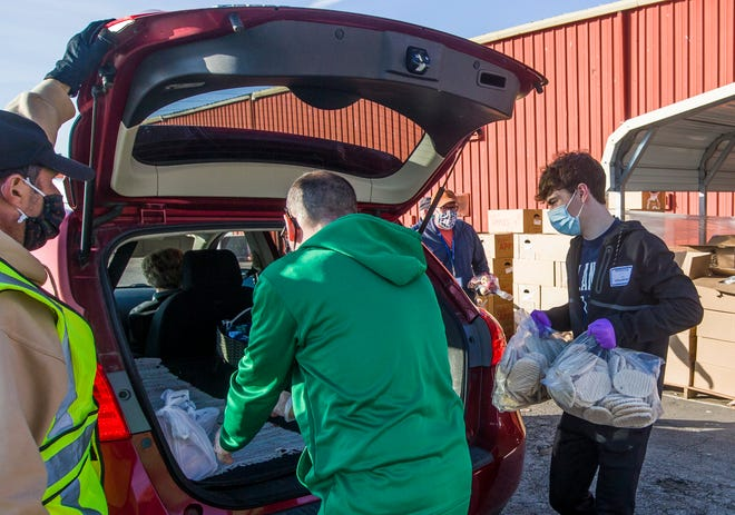 Volunteers at the Food Bank of Northern Indiana distribute food during a weekly drive-thru event on Nov. 12, 2020, in South Bend.