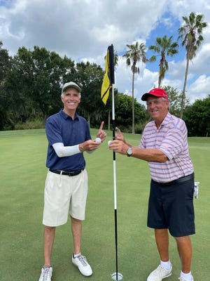 David Brown and Georges Lussier stand over the 15th hole at Heritage Oaks Golf & Country Club and hold the two balls hit on consecutive holes-in-one last week in an FSGA one-day tournament. The odds of consecutive aces are 17 million to 1. COURTESY PHOTO