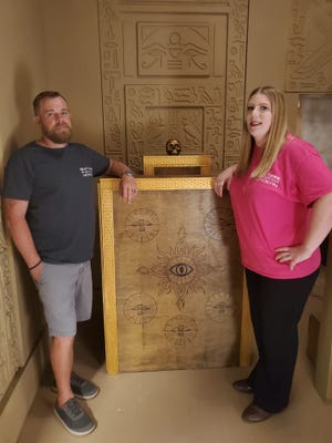 Eric and Brittany Taylor stand in their newest escape room Secrets of the Pharaoh, which will open soon.