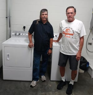 """Dale """"Boomer"""" Salsberry (left), head of the board of trustees of Uhrichsville Eagles Aerie No. 2264, and Robert """"Buck"""" Cottrell, administrator of Uhrichsville Moose Lodge No. 740 are shown with a new washer and dryer the organizations bought for Claymont Stadium."""