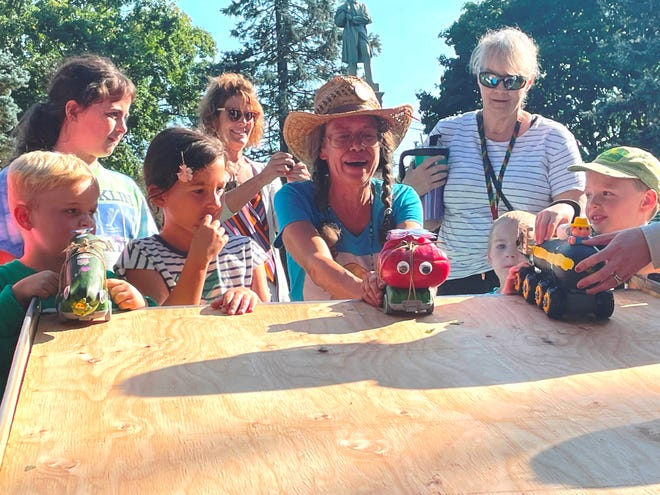 Linda Noel, of Linda's Tomatoes, prepares to race her googly-eyed tomato vehicle against zucchini racers in one of the Zucchini Races at the Franklin Farmers Market on Sept. 10.