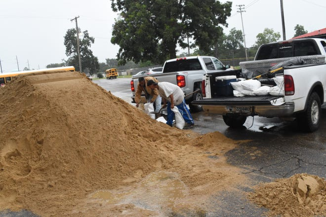 John David Lacour (left) and Doc Bane fill sandbags at Cheatham Park on Jones Avenue Tuesday morning. Tropical Storm Nicholas is set to move through the area bringing with it heavy rains and possible flooding.