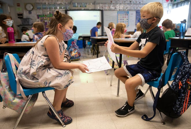 First graders Ella Siciliano, left, and Crosley Roewer, share their work during an assignment in Julie Fischer's first-grade class at J.F. Burns Elementary, Aug. 31, 2021. The school is in the Kings Local Schools District outside Cincinnati, which has have mandated masks for pre-K through sixth grade.
