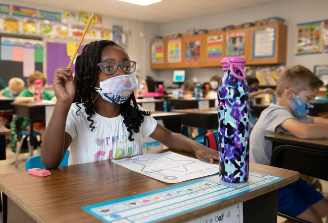 First-grader, Joy Olugu listens to her teacher, Julie Fischer, at J.F. Burns Elementary, Aug. 31, 2021. Kings Local Schools have mandated masks for pre-K through sixth grade. As students walk into the classroom, they use hand sanitizer to clean their hands.