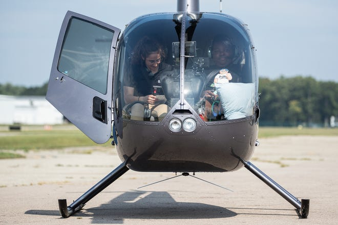 Michigan Helicopter pilot Caitlin George, left, checks the helicopter before taking Torrance Johnson, 15, of Detroit for a ride at Oakland County International Airport in Waterford Township on Sept. 14, 2021.