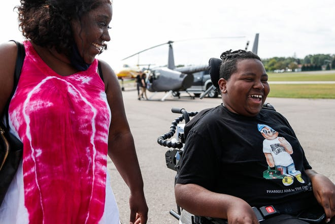 Katrina Johnson of Detroit watches her son Torrance Johnson, 15 with a smile on his face as they leave the Oakland County International Airport after a helicopter ride hosted by the D-Man Foundation in Waterford Township on Sept. 14, 2021.