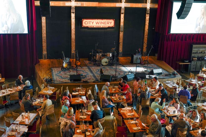 """In this Thursday, June 24, 2021 file photo, patrons dine at City Winery in New York. If your summer of """"revenge"""" spending has come for a payback of its own in the form of lingering debt, make a plan for paying it off."""