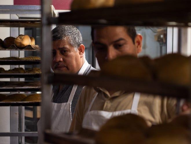 El propietario de Panaderia San Miguel, Miguel Ochoa, izquierda, y Jaime Neri, derecha, ambos de Evansville, revisan los pasteles después de salir del horno en Panaderia San Miguel en Evansville, Indiana, el martes por la mañana, 14 de septiembre de 2021. La panadería se especializa en auténtica comida mexicana. bollería y pan En una ciudad con una población hispana de más de 3000.