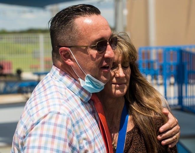 Harns Marsh Middle School Principal Alex Dworzanski gives a supportive embrace to testing coordinator Laura Davis after she spoke to the media at the school on Tuesday, September 14, 2021. She thwarted a possible school shooting by seeing something and saying something to school officials. Two students at the school were arrested charged with conspiracy to commit a mass shooting.