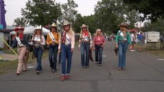 A group of rodeo queens walks the midway, greeting patrons at the Wyoming State Fair in Douglas, Wyoming on Aug. 17, 2021.