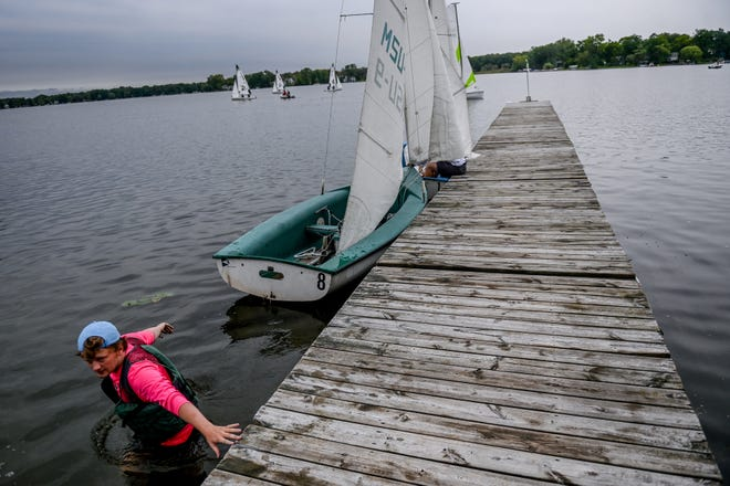 Michigan State University student Lochlyn Reed walks in the water next to the dock at the Michigan State University Sailing Center as he prepares his boat to sail on Monday, Sept. 13, 2021, on Lake Lansing in Haslett.