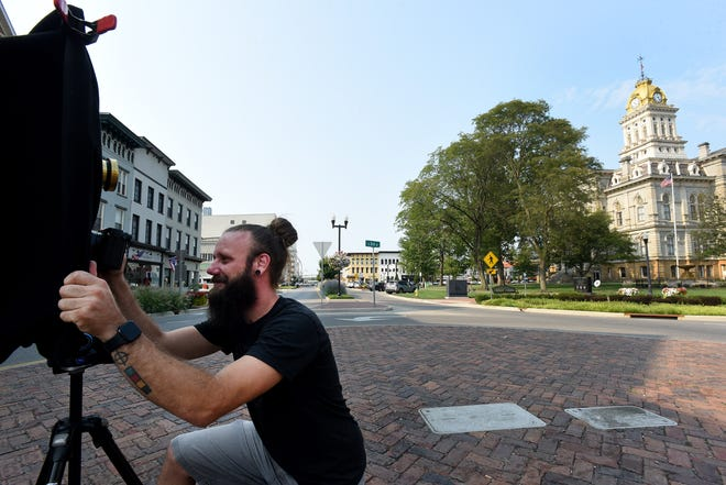 Creative director for Explore Licking County and local photographer, Garrett Martin places a digital camera beneath the lens on his camera obscura to take a picture of the Licking County Court House. Martin built the camera using a historic lens from the 1900s as part of a project to capture sites around Licking County for ELC. Before working for ELC Martin taught photography courses and ran his own photography company, Martin Digital.