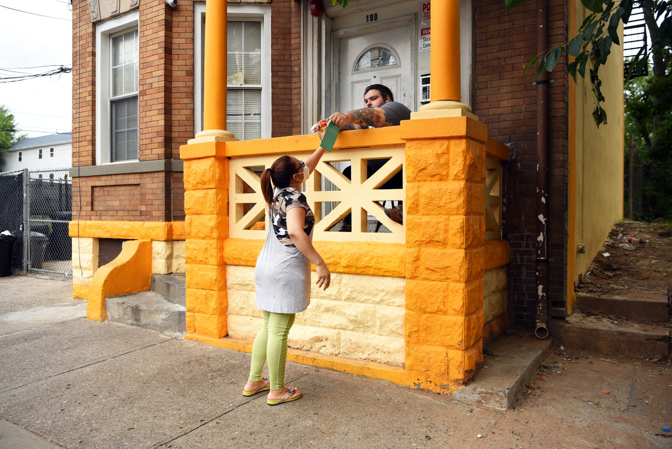 Elias Arroyo, 32, accepts a meal from his neighbor, Jennifer Perez, while sitting outside of his Hamilton Avenue apartment in Paterson on Aug. 28, 2021. Arroyo moved to the neighborhood a year ago from Washington Heights in upper Manhattan, and says things have quieted down since Perez, Peralta and the other families living in the Hamilton 7, a group of Habitat for Humanity homes on the street, have moved in.