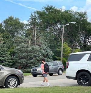 With cars moving west to east or parked along the side of the road a Salem High student crosses a busy Joy Road as school lets out on Sept. 14, 2021.