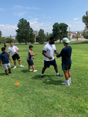Deylon Williams coaching youth athletes on proper defensive techniques.