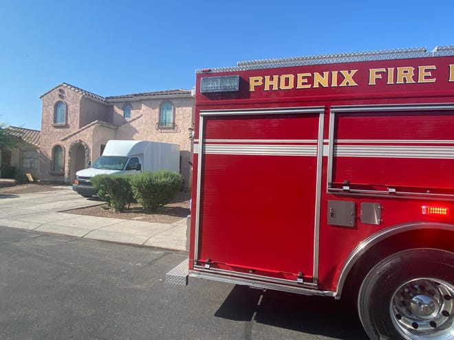 A Phoenix Fire engine parked outside of a burning building