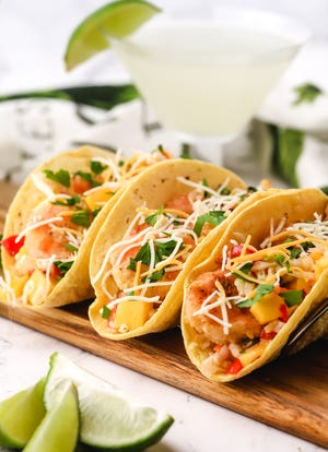 These tacos are full of fried shrimp, juicy mango, fresh tomato, avocado, and crunchy shredded cabbage.