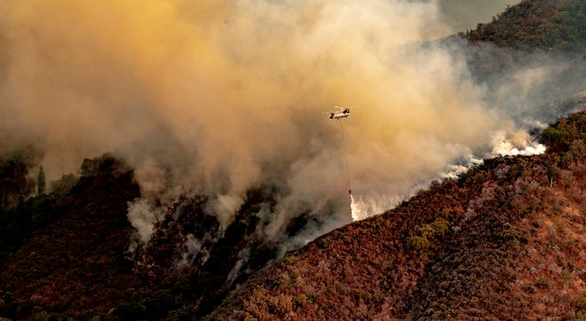 Steam rises behind a helicopter dumping river water Monday, September 13, 2021 on the KNP Complex Fire as seen from Amphitheater Point in Sequoia National Park.