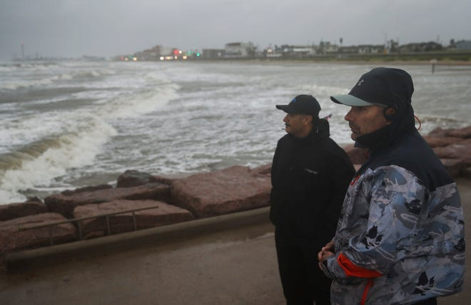Jaime Ybarra, right, and his friend Frank Rivera watch their lines as they fish as Tropical Storm Nicholas moves toward the Texas coast. Nicholas formed into a Category 1 hurricane late Monday.
