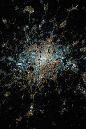 London at night, as seen from the International Space Station. Different colors are visible, showing different lighting technologies.