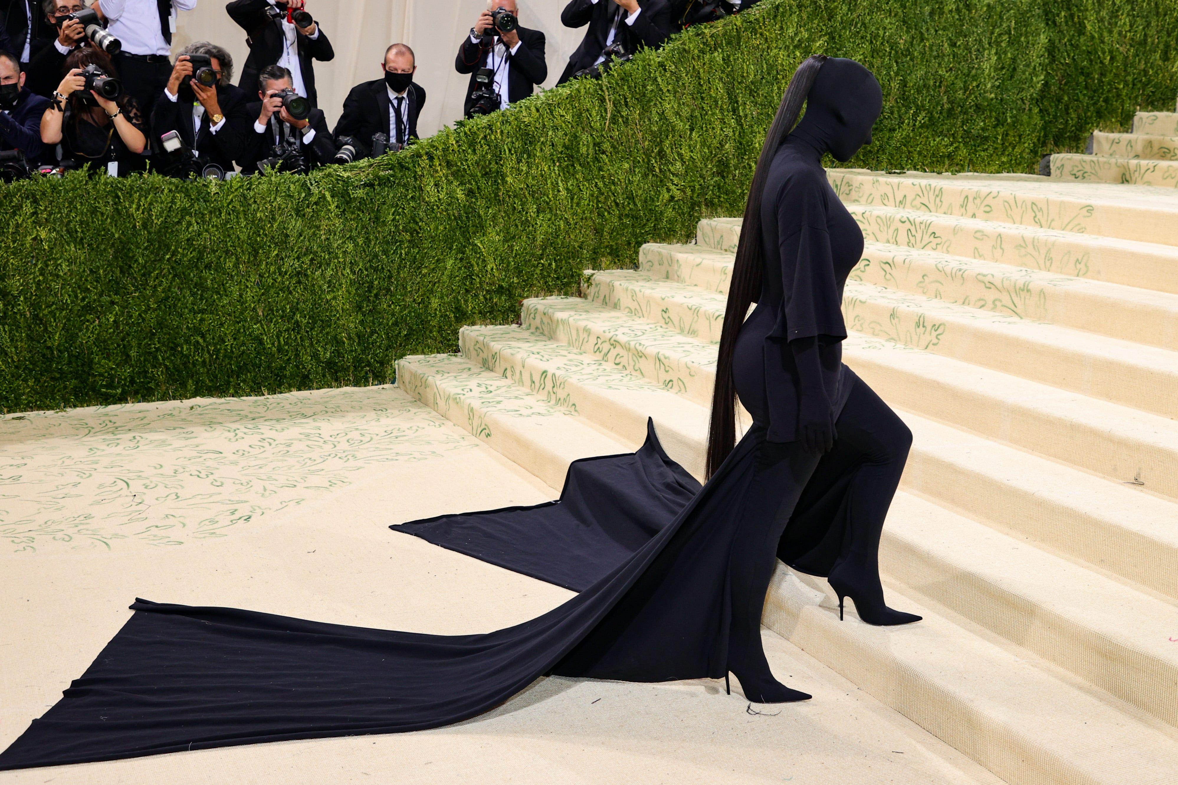 Kim Kardashian walks up the steps covered in black fabric.