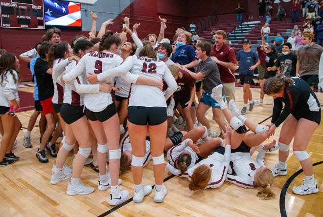 The Austin High volleyball team and fans celebrate after the District 26-6A volleyball game against Lake Travis on Tuesday at Austin High School. The Maroons rallied for a 5-set win after dropping the first two sets.