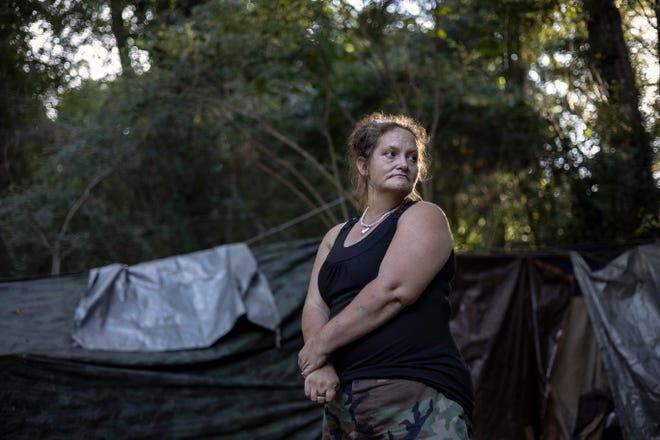 """Flora Harlow, who has been in and out of permanent housing over the past several years, stands near her tent on Thursday, Sept. 9, 2021 in Athens. Harlow and others live in a small encampmentcolloquially called """"Cooterville,"""" a wooded area under CSX's train tracks off Willow Street that is scheduled to be clearedby Nov. 12."""