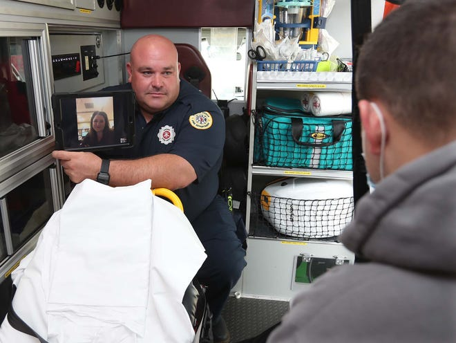 Firefighter/paramedic Adam Lovell holds a tablet showing Dr. Holli Hill via the Akron Fire Department's new telehealth program during a demonstration with firefighter/paramedic Dan Hilton portraying the patient.