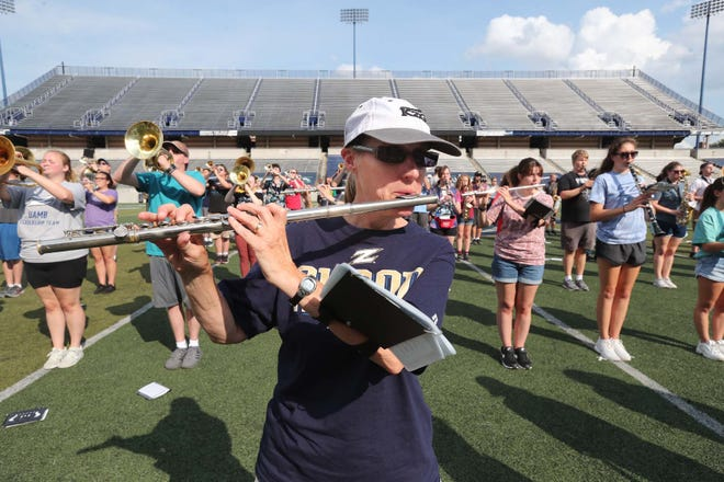 Marcia Korane, 56, of Hudson, plays the flute during a practice of the University of Akron Marching Band at InfoCision Stadium. Korane joined the marching band after her daughter graduated last year.