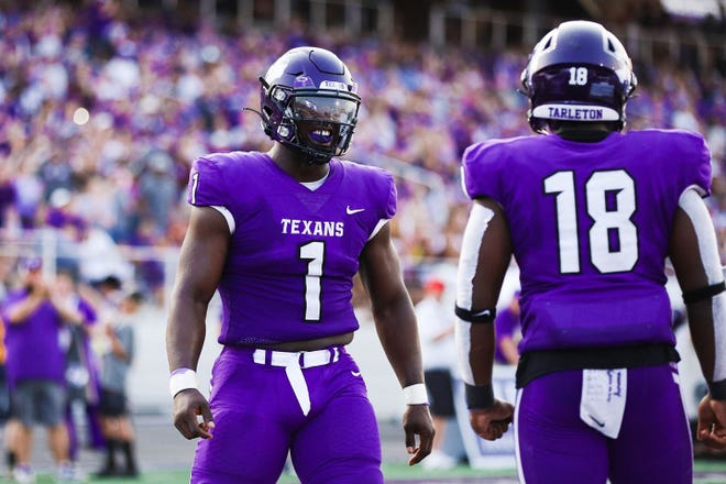 Senior wide receiver Tariq Bitson (No. 1) and sophomore linebacker D.J. Harris (No. 18) talk things over during last week's blowout win over Fort Lewis.