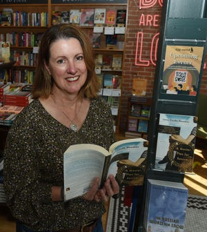 Ana McCracken, the founder of Ames Writers Collective, poses with the books at Dog-Eared Books Wednesday, Sept. 15, 2021, in Ames, Iowa.