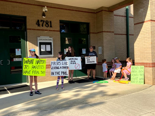 A small crowd gathers outside the Columbia County Board of Education meeting Tuesday night to protest the mask mandate approved by the board Aug. 24.