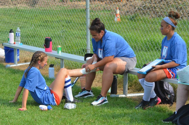 First-year Millville field hockey coach Corrinne Etter-Veight shows her players how to record a recent game is pressed into service taping the ankle of junior captain Stella Sheppard