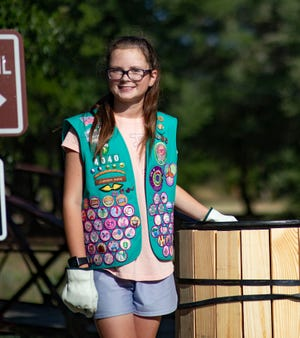 Karissa Raines is pictured with one of the trash cans installed along the walking trails at Festival Park.