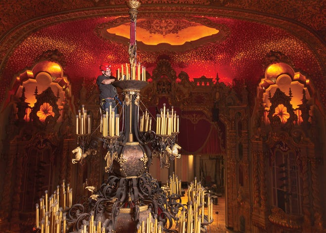 Scott Hinch, with Local 12 of the International Alliance of Theatrical Stage Employees, cleans the top of the massive chandelier in the Ohio Theatre. The fixture was lowered June 14 for cleaning and so light bulbs could be replaced. The process generally happens every two years but was postponed during the pandemic.