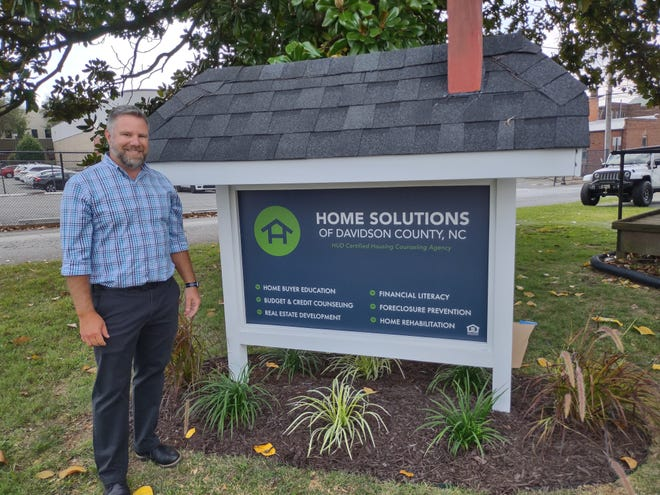 Toby Prince, executive director at the former Lexington Housing CDC, stands in front of the sign with the new name of the organization on its 25th year anniversary.