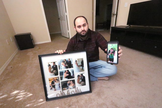 Chris Smith sits with some of his wedding photos and a cellphone photo of his wife Ashley's son from a previous relationship, Gabriel.  Ashley miscarried the couple's child after she was hospitalized with COVID-19. She died Sept. 10, and soon after Gabriel went to live with his biological father.