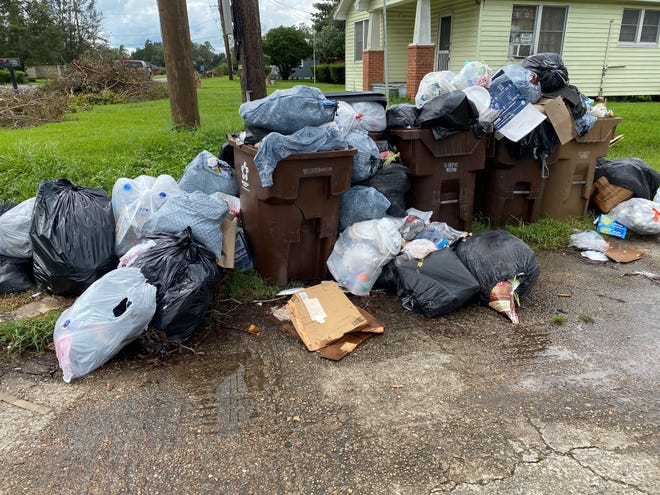 Garbage overflows from cans at an apartment complex on East Bayou Road (Hwy. 308) late in the afternoon Sept. 15 in Donaldsonville.