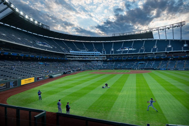 Kansas City Royals starting pitcher Jackson Kowar, lower right, warms up in the outfield before the start of Tuesday's game against the Oakland Athletics at Kauffman Stadium. The Royals announced Tuesday that they're exploring the possibility of a new baseball stadium in downtown Kansas City.