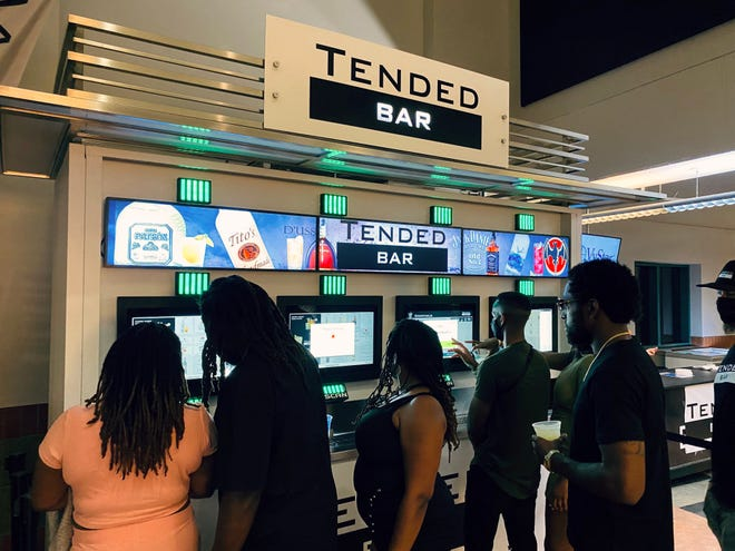 Fans at a recent concert at Daily's Place select their beverages from touch screens on a TendedBar, an automated drink service machine.